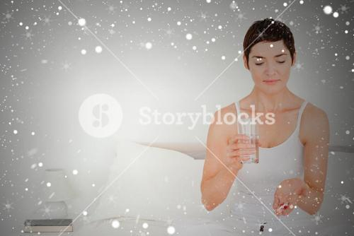 Composite image of charming woman taking pills