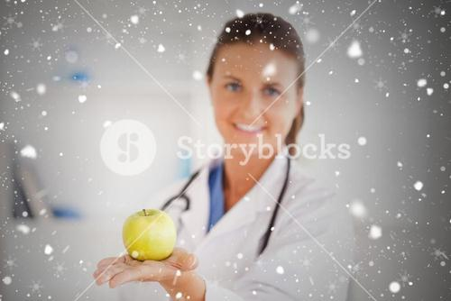 Doctor with stethoscope holding an apple looking at the camera