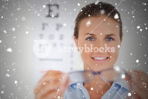 Brunette eye specialist handing out glasses looking into the camera