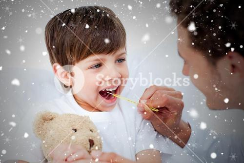 Composite image of positive doctor taking little boys temperature
