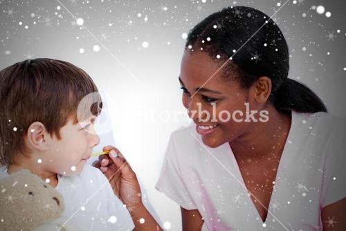 Composite image of smiling doctor taking childs temperature