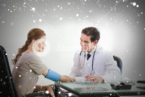 Composite image of doctor taking blood pressure of a patient