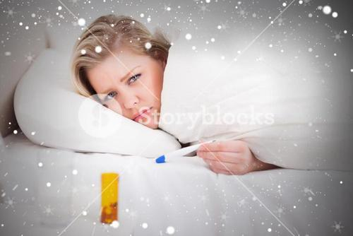 Composite image of sick blonde woman with a thermometer