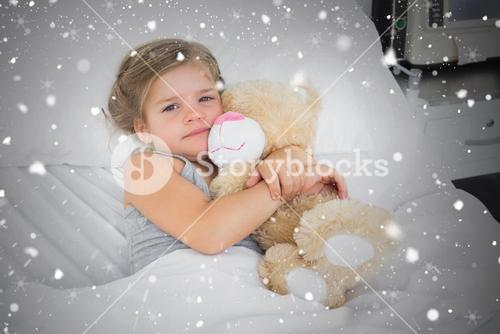 Composite image of cute girl embracing teddy bear in hospital bed