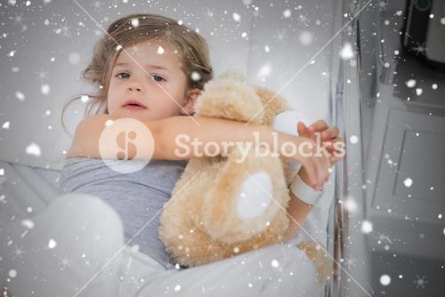 Composite image of cute girl hugging teddy bear in hospital bed