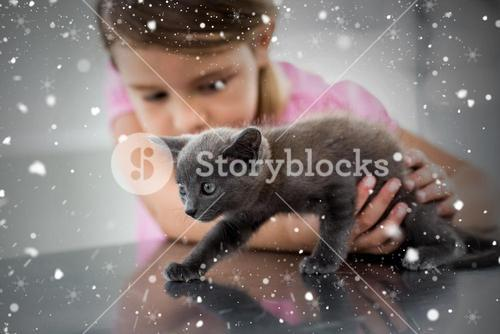 Composite image of girl playing with kitten