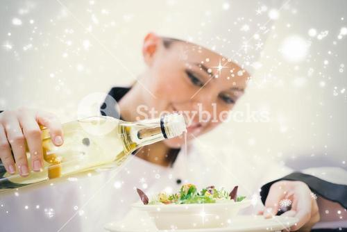 Smiling woman chef dressing a salad