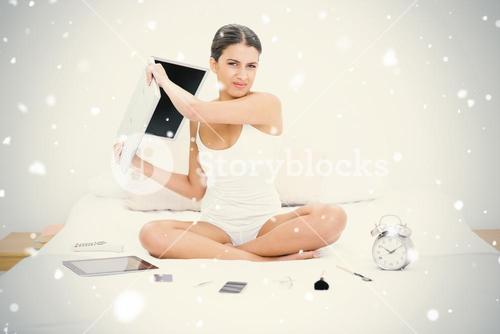 Furious young brown haired model in white pajamas throwing her laptop