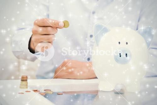 Mid section of a man putting some coins into a piggy bank