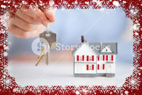 Woman holding keys next to a model house
