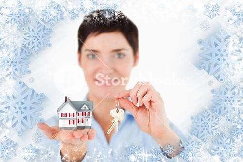 Close up of a woman showing keys and a miniature house