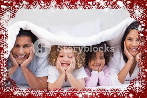 Composite image of family hiding under the blanket