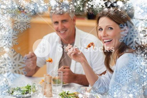 Composite image of laughing couple eating dinner