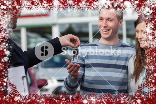 Composite image of couple receiving car keys by a dealer