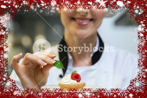 Smiling head chef putting mint leaf on little cake on plate