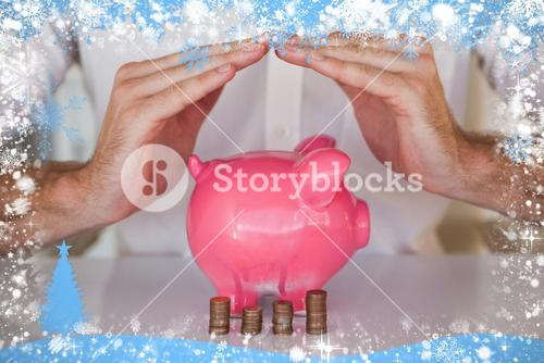 Composite image of casual businessman sheltering piggy bank and coins