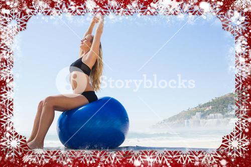 Fit blonde sitting on exercise ball at the beach