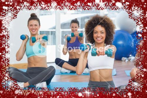 Portrait of a fit class lifting dumbbell weights