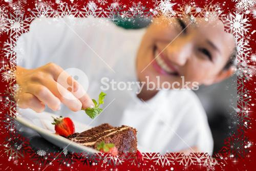 Smiling female chef garnishing food