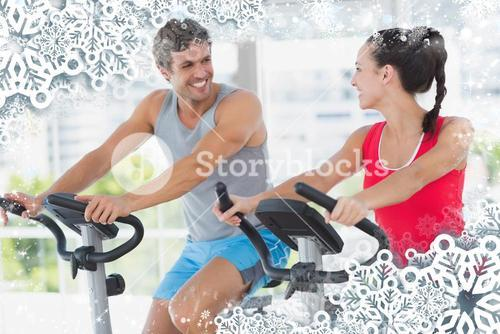 Smiling couple working out at spinning class