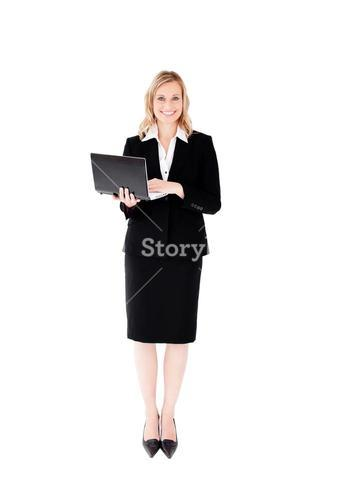 Delighted businesswoman using her laptop standing