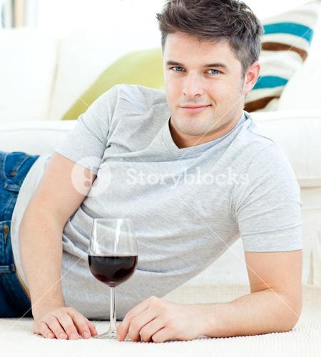 Handsome young man with wineglass lying on the floor