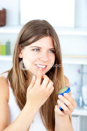 Pretty woman using vaseline for her lips
