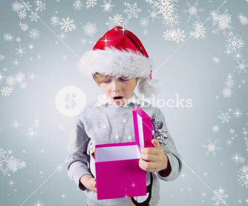 Composite image of cute festive boy opening present