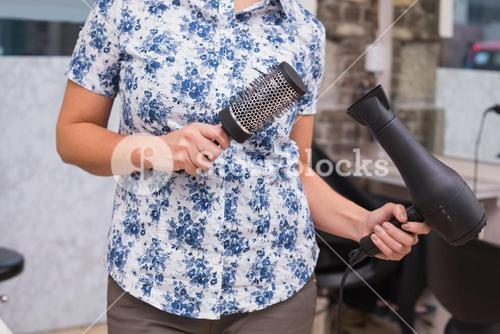 Hairdresser holding brush and hairdryer