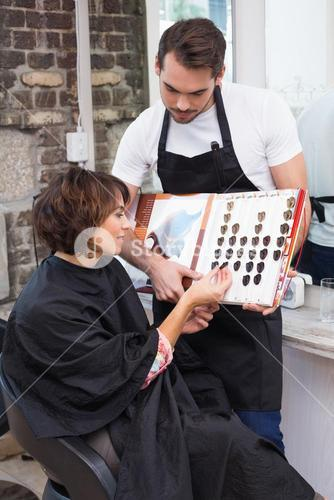 Pretty brunette picking out hair colour with stylist