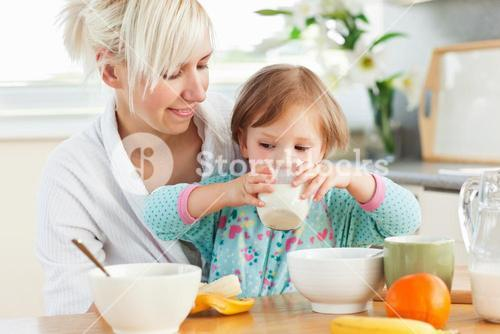 Radiant woman having breakfast with her daughter
