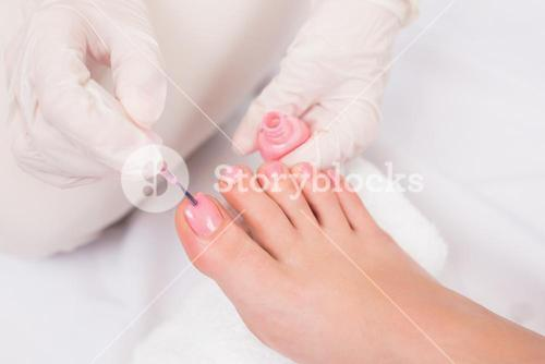Woman getting her toenails painted
