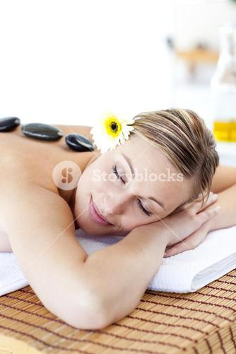 Close up of a woman with hot stone on her back and closed eyes