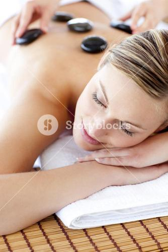 Glad woman receiving a massage with hot stone