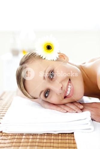 Jolly young woman with flowers in her hair on a massage table