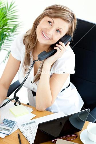 Selfassured businesswoman talking on phone sitting at her desk