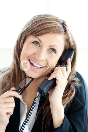 Confident young businesswoman talking on phone sitting