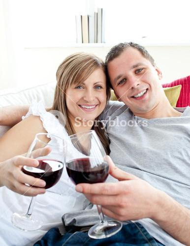 Loving young couple drinking wine sitting on a sofa