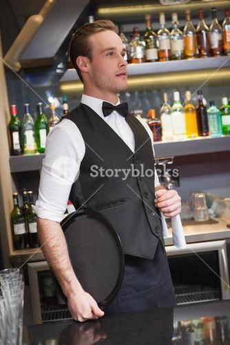 Serious waiter holding tray and towel
