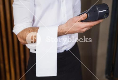 Handsome waiter holding credit card machine