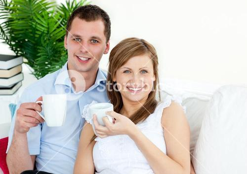 Cheerful young couple drinking coffe sitting on a sofa smiling at the camera