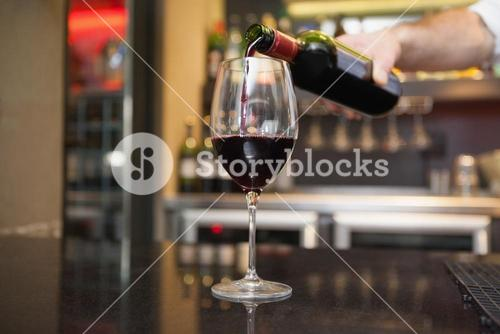 Hand pouring red wine into glass