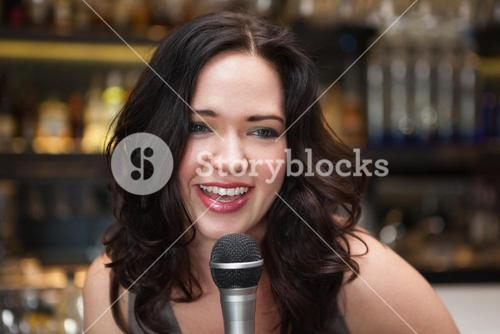 Happy brunette singing into mic