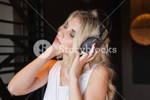 Pretty blonde listening to music with eyes closed