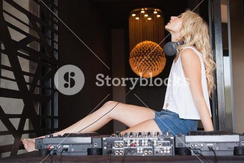 Sexy DJ girl with eyes closed sitting behind the decks