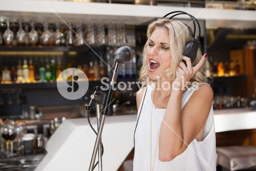 Woman with headphone singing while closing her eyes