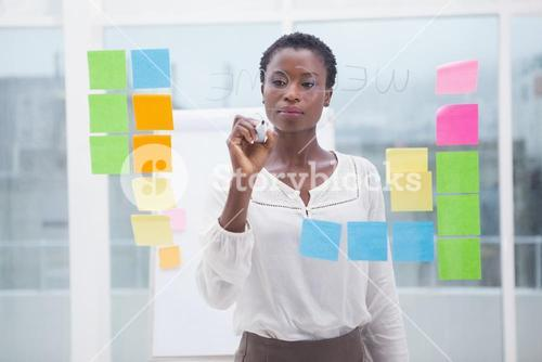Businessman with short hair writing on clear board