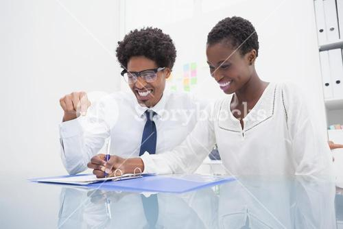 Happy coworkers looking the document
