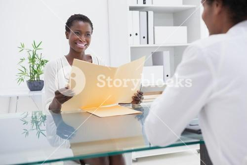 Smiling coworkers studying a document