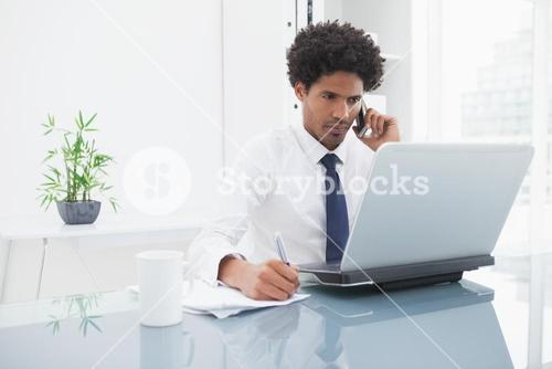 Businessman phoning and writing notes